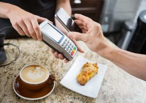 image of customer paying through mobilephone over electronic reader at cafe counter